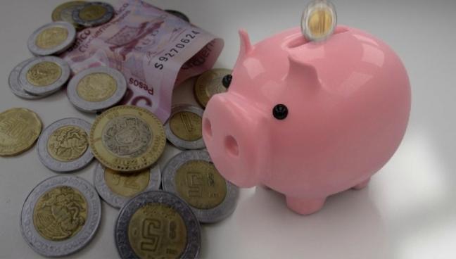 monedas-y-billetes-mexicanos-junto-a-alcancia
