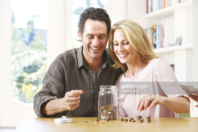 Middle aged couple counting coins into jar